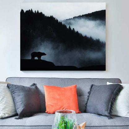 Canvas print of bear on mountain above living room sofa.